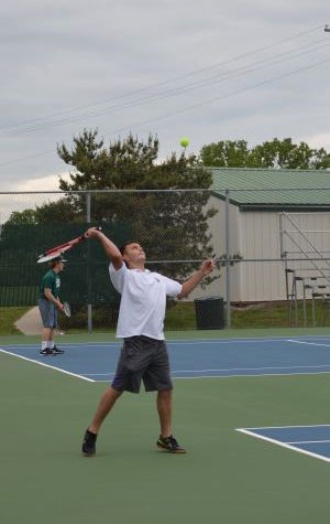 Sophomore JV player Tucker Austin sends a powerful serve to his opponent at the De Soto courts.