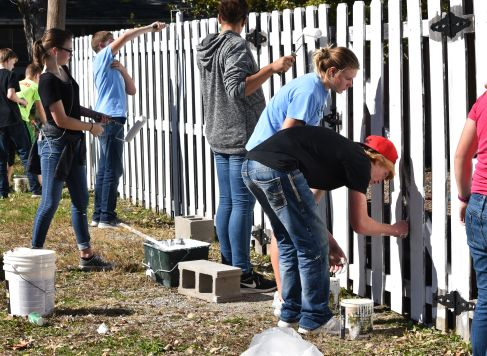 BHS freshman helping the community on Community Service Day by repainting a fence down town.