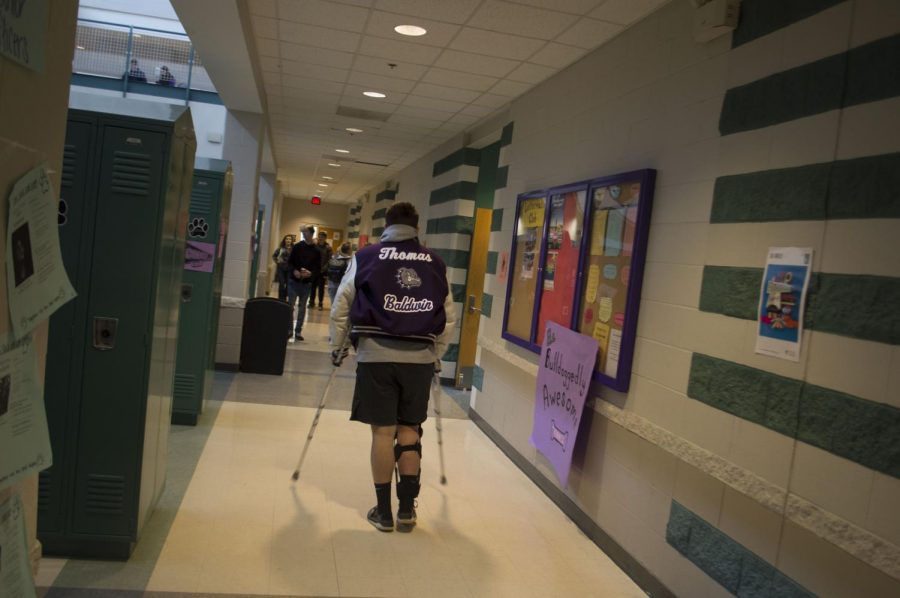 Sophomore Toby Thomas pictured wearing his letterman jacket while on crutches.  Thomas had previously injured himself during his wrestling season tearing his meniscus.