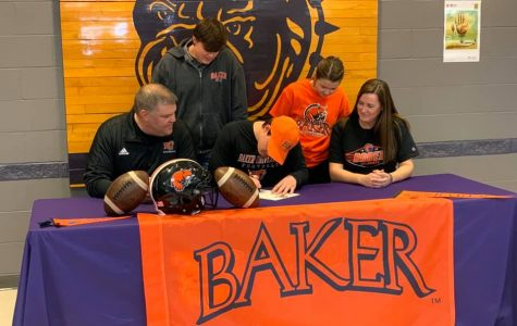 Senior Alex Berg signs to become a Baker Wildcat next year, suiting up for the football team. Seated next to Berg are his parents, both also BU alumni.